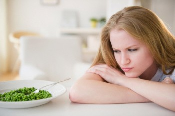 USA, New Jersey, Jersey City, Woman leaning on table looking on green peas